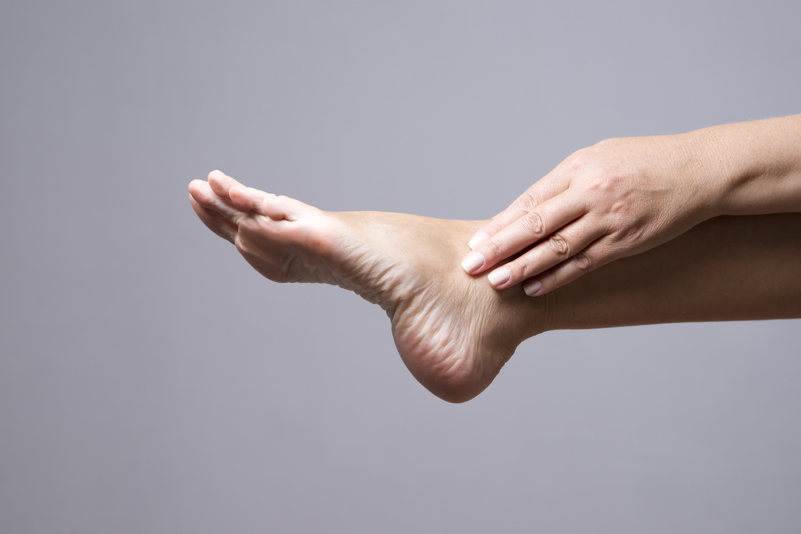 Pain in the foot. Massage of female feet on a gray background