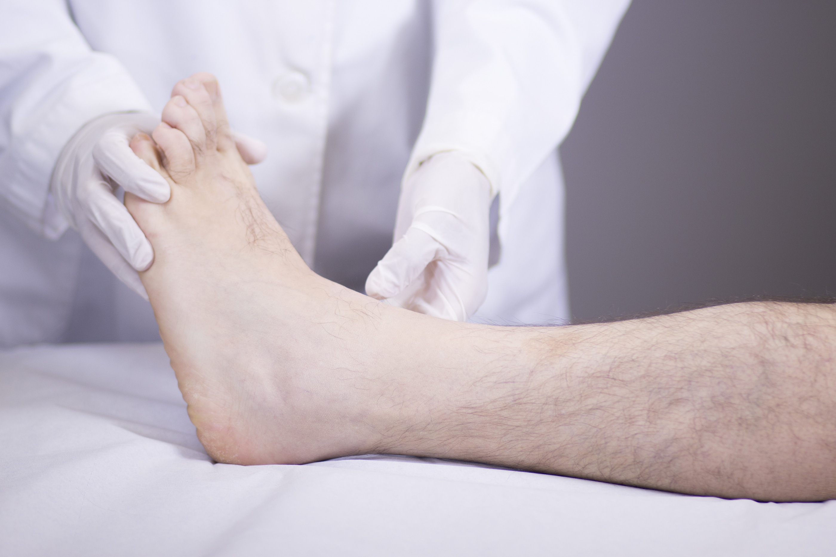 Traumatology and orthopedics surgeon in doctor and patient orthopedic medical examination consultation of foot ankle and toes in hospital clinic. ** Note: Shallow depth of field