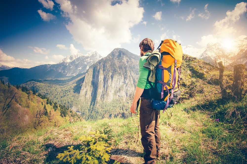 Young Man Traveler with backpack relaxing outdoor with rocky mountains on background Summer vacations and Lifestyle hiking concept