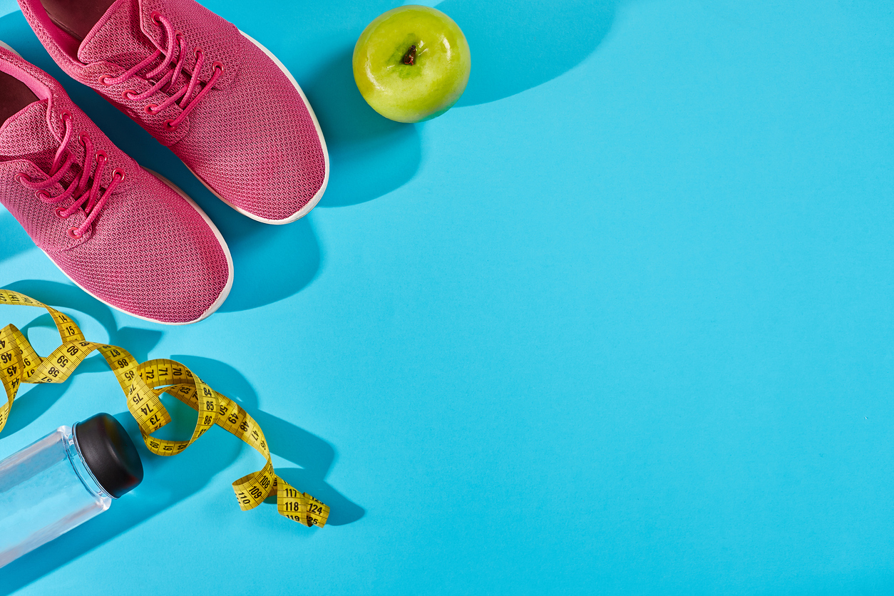 Sneakers with measuring tape on cyan blue background. Centimeter in yellow color near pink trainers, close up. Sport shoes and sportive equipment for healthy shape. Sports and healthy lifestyle concept