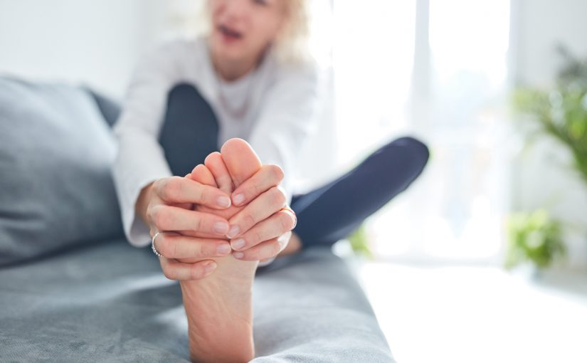 Woman holding numbness in toes