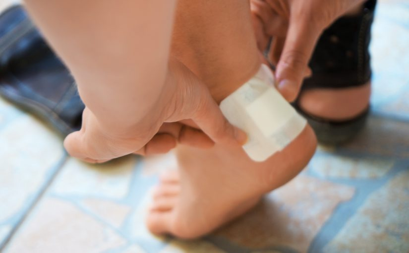 Person putting bandage on heel to prevent blisters