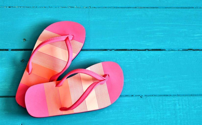Pair of pink flip flops on blue wood texture background