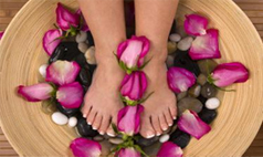 woman soaking her feet in dish with flowers stock photo